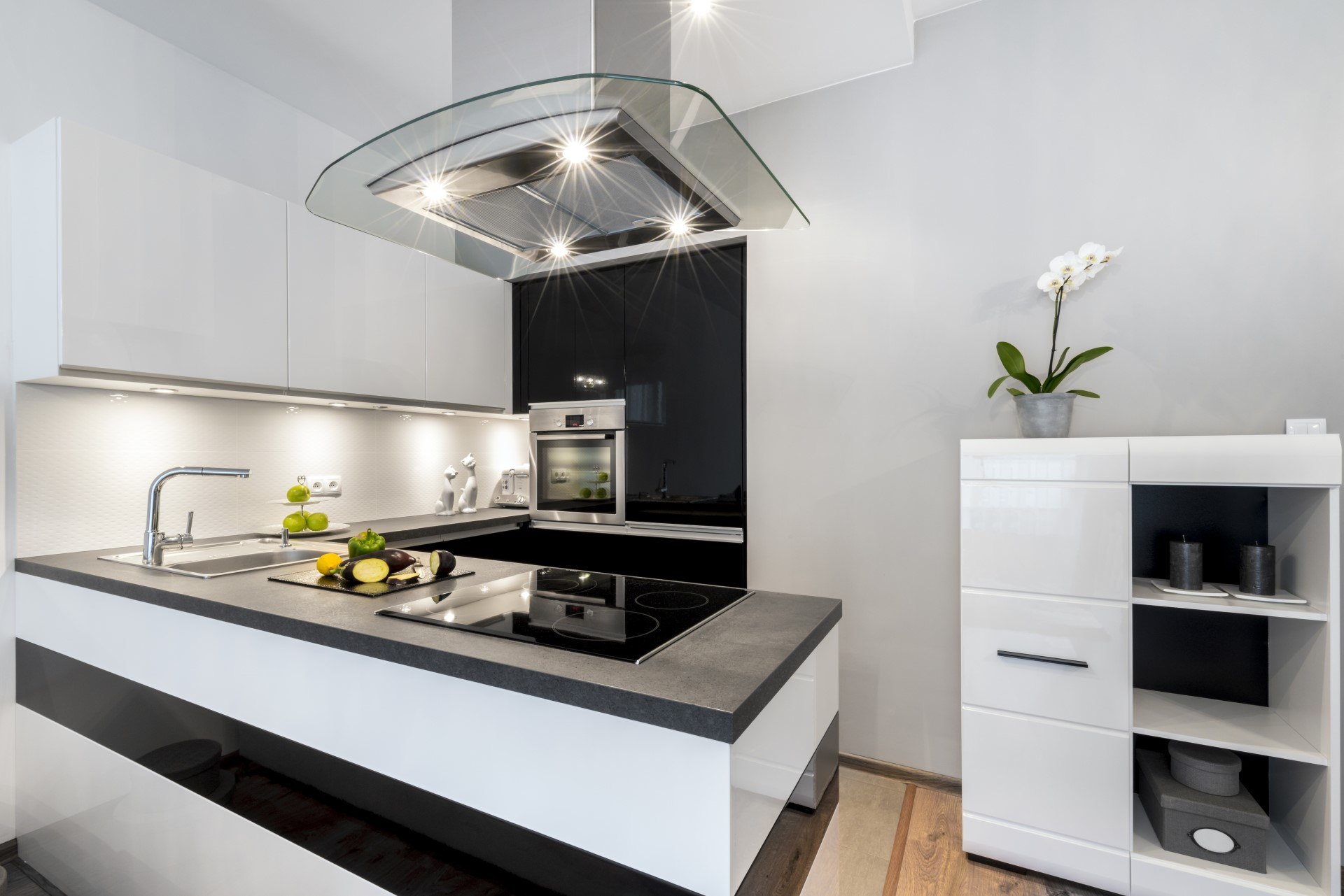 If you're looking for that edgy and cool kitchen layout, this modern design nails it. It comes with a useful functionality of using darker colors for the heavy traffic areas followed by lighter colors which help brighten everything. The glass style range hood is pretty cool too.