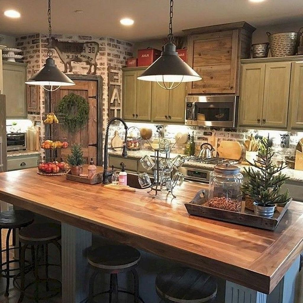 A farmhouse kitchen with a brick wall and natural wood slab island countertop with seating is a great way to warm up your kitchen. Add lighting above the island and countertops to really bring out farmhouse decor.